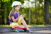 istock Pretty little girl learning to skateboard on beautiful summer day in a park. Child enjoying skateboarding ride outdoors. 938285446