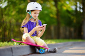istock Pretty little girl learning to skateboard on beautiful summer day in a park. Child enjoying skateboarding ride outdoors. 942476830