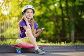 istock Pretty little girl learning to skateboard on beautiful summer day in a park. Child enjoying skateboarding ride outdoors. 952014700