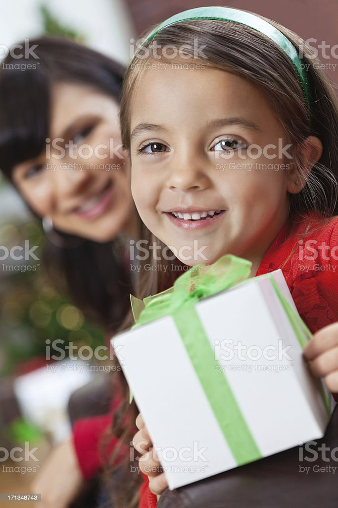 Pretty little girl opening Christmas present with mom royalty-free stock photo