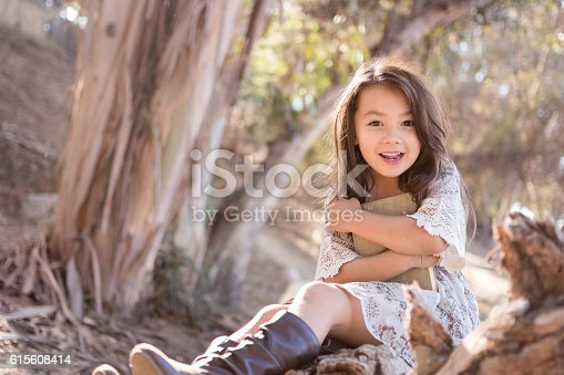 istock Pretty little girl outdoors excited about reading a book 615608414