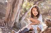 A pretty little girl is sitting on a fallen tree in a forest. She's excitedly holding a book, which she is about to read. The girl is 6 years old and of Eurasian descent.