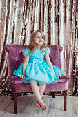 Pretty little girl posing against the golden background. Fashion photo. Christmas, birthday, party time.