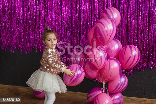Pretty little girl plays with pink balloons