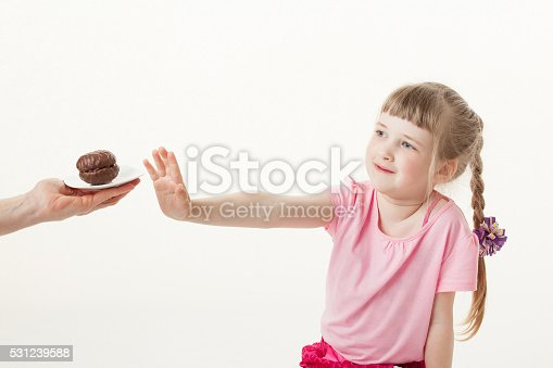 Pretty little girl regecting a chocolate cake, white background