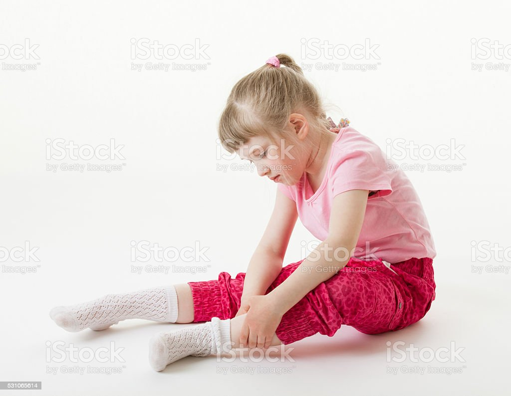 Pretty little girl trying on sock, white background stock photo