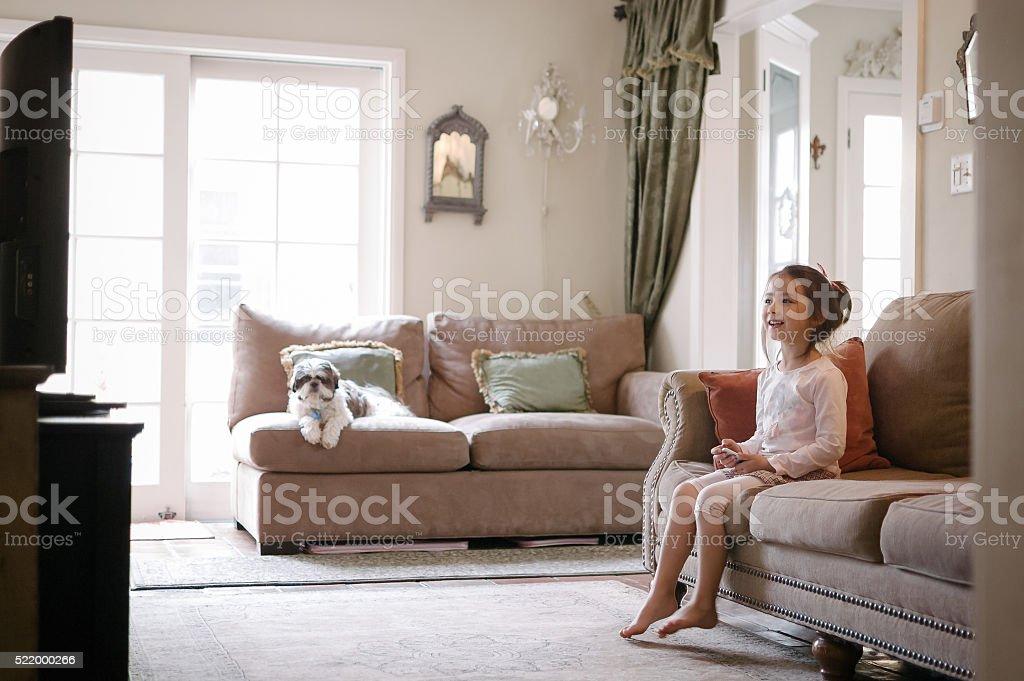 Pretty little girl watching TV on Apple TV stock photo