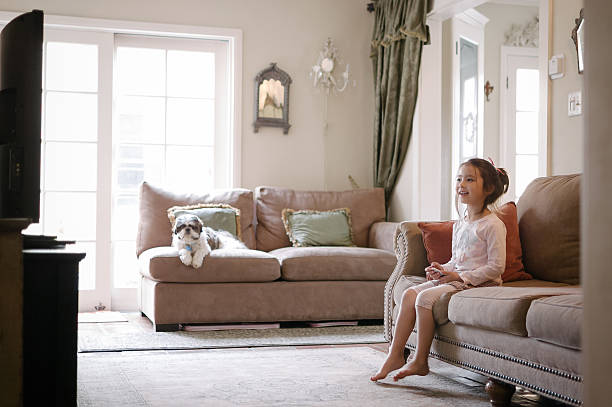 hübsches kleines mädchen vor dem fernseher mit apple tv - kids tv zimmer stock-fotos und bilder