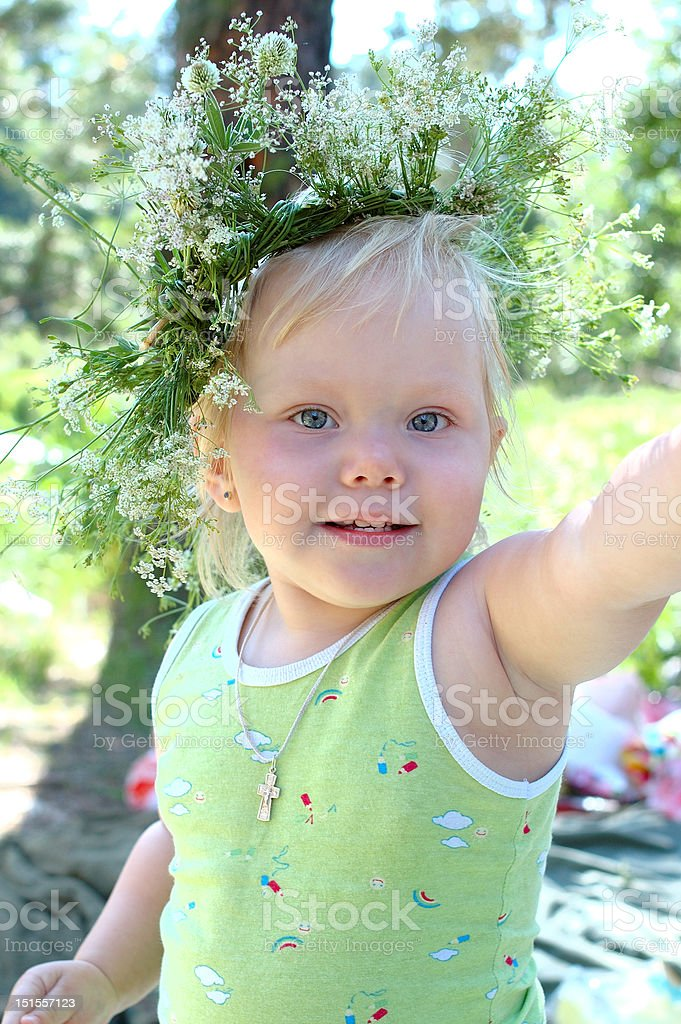 Pretty little girl with field flower garland. royalty-free stock photo