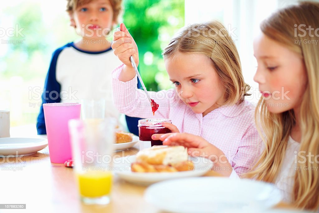 Pretty little girl with her family removing jam from bottle royalty-free stock photo