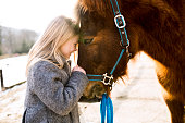 istock Pretty little girl with horse on sunny winter day. 646559176