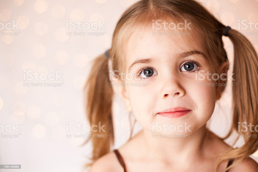 Pretty little girl with twinkle lights behind her royalty-free stock photo