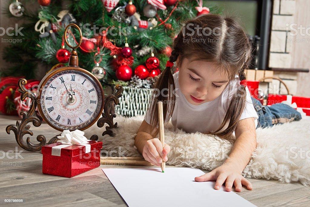 Pretty little girl writes letter to Santa  near christmas tree stock photo