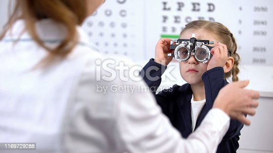 Pretty little schoolgirl visiting oculist for measuring eyesight with phoropter