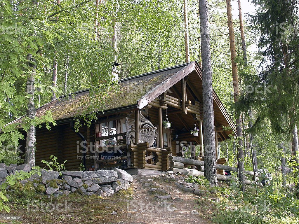 A pretty log cabin in the woods stock photo
