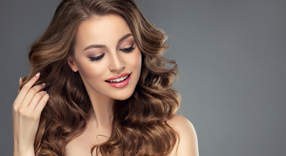 Pretty looking model is smiling tenderly and touching own hair. Young woman with long, dense, freely laying hairstyle and perfect makeup. Hairstyle, frizzy hair and cosmetic.