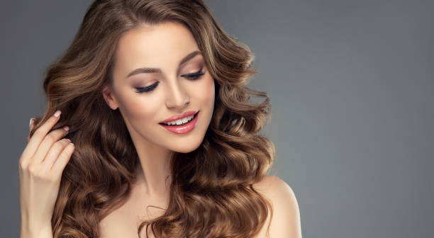 Pretty looking model is smiling tenderly and touching own hair. Frizzy hair. stock photo