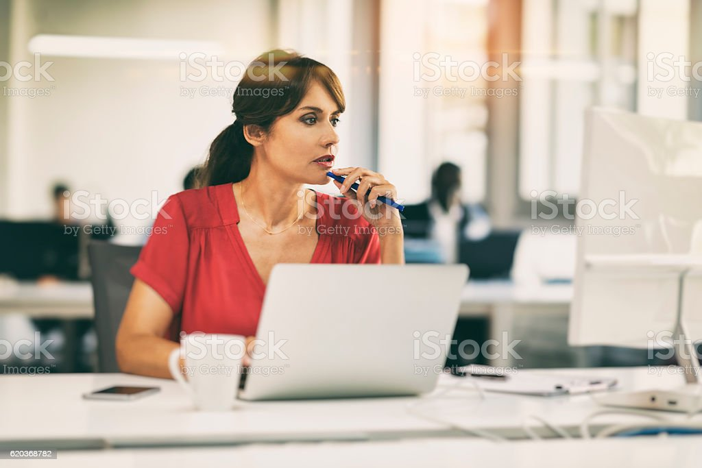 Pretty mature businesswoman focused on computer screen in startup stock photo