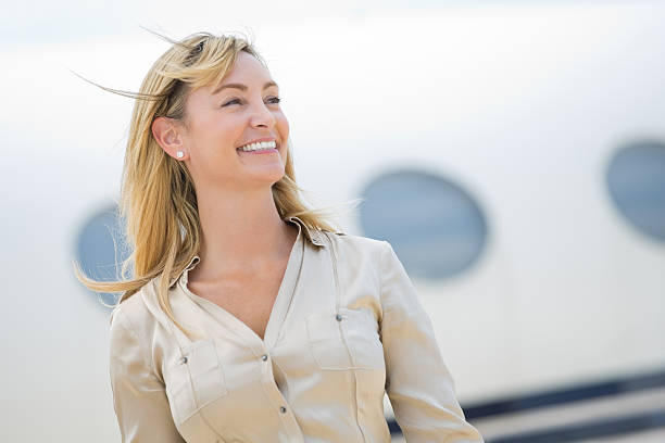 Pretty mature woman preparing to board private jet stock photo