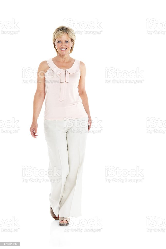 Pretty mature woman walking on white background stock photo
