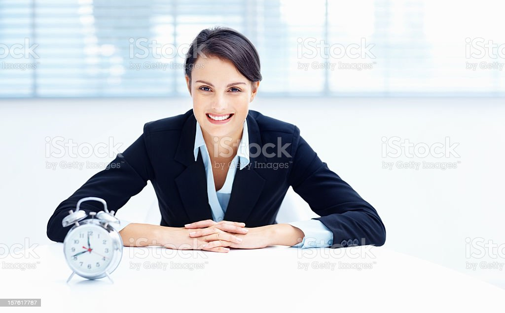Pretty middle aged executive with an alarm clock on desk royalty-free stock photo
