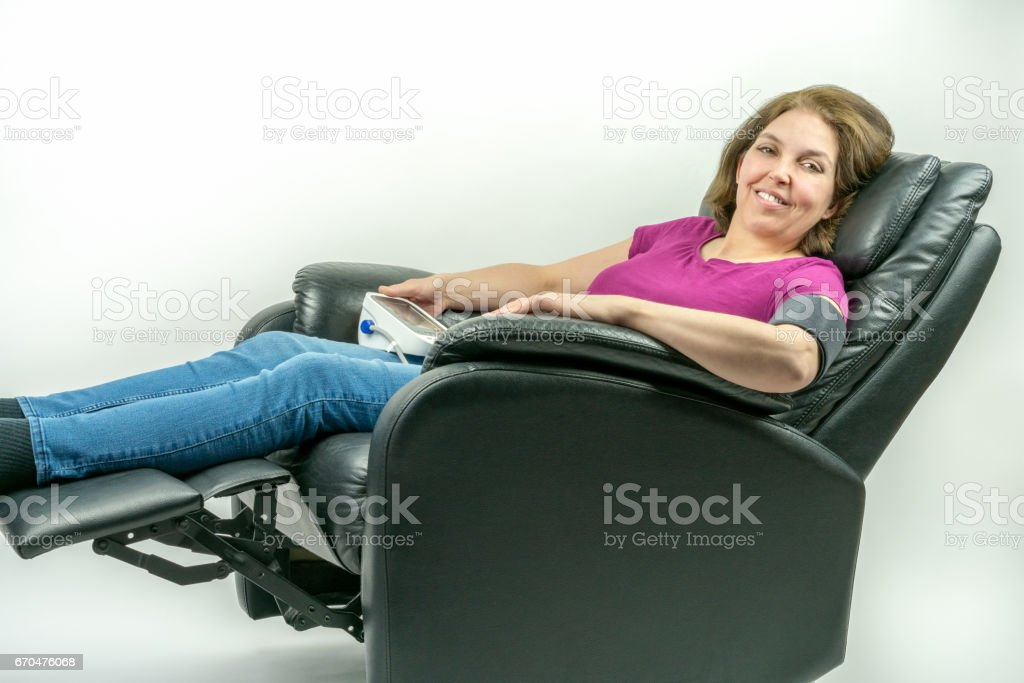 Pretty middle-age woman leaning back in black leather recliner armchair. Checking blood pressure using portable blood pressure machine. stock photo