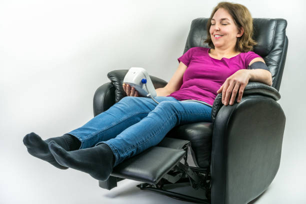 Pretty middle-age woman resting in black leather recliner armchair. Checking blood pressure using portable blood pressure machine. stock photo