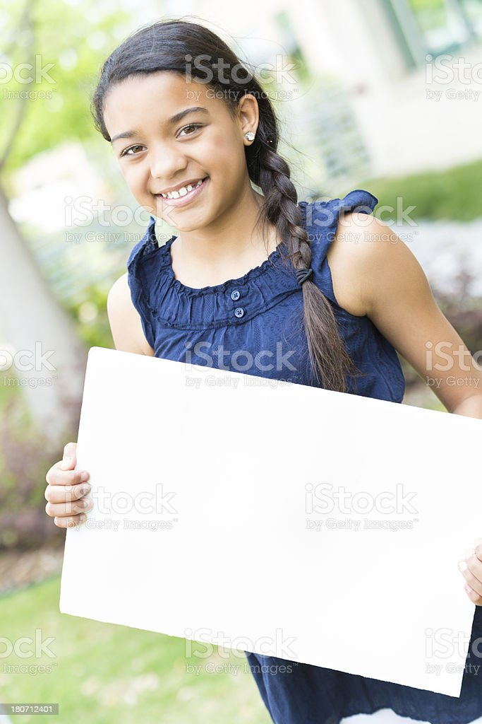 Pretty mixed race preteen girl holding blank sign outdoors stock photo