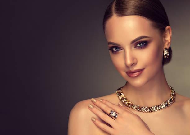 pretty model with smoky-eyes makeup style is demonstrating gilded jewelry set. - kamień szlachetny zdjęcia i obrazy z banku zdjęć