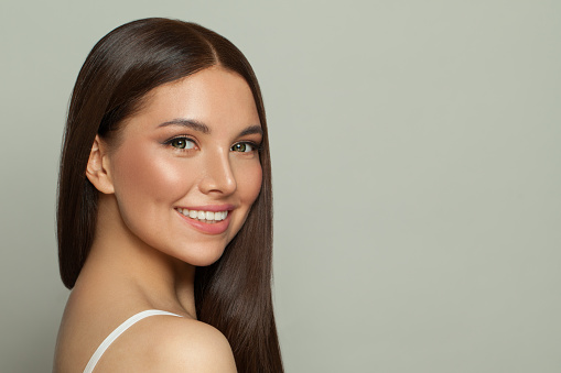 Pretty model woman with clear skin and long healthy straight hair. Skincare and facial treatment concept