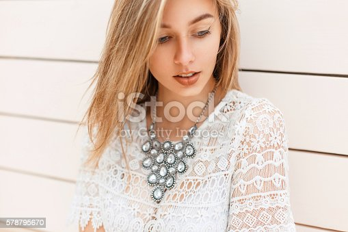 578791454istockphoto Pretty modest woman in vintage lace blouse near white wall 578795670
