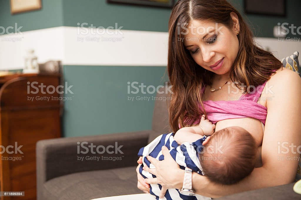 Pretty mom breastfeeding her baby - Stock image .