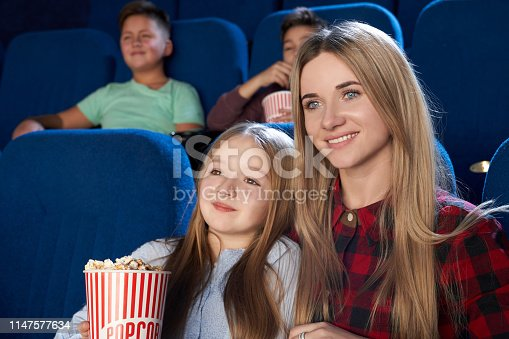 istock Pretty mother and daughter watching film in cinema. 1147577634