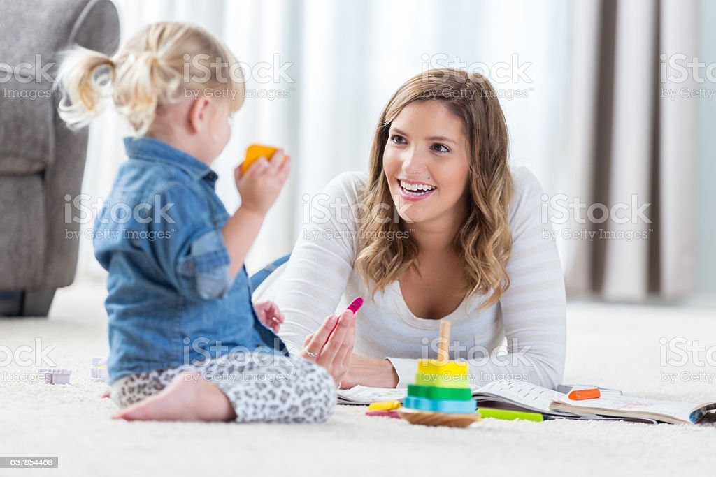 Pretty mother and her preschool age daughter play together stock photo