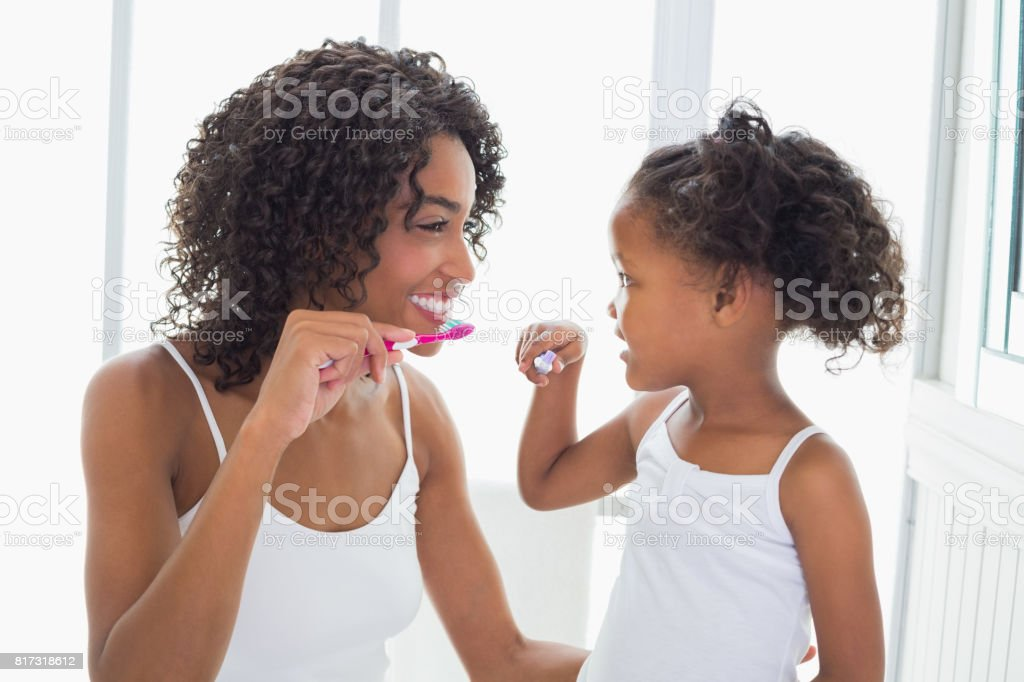 Pretty mother with her daughter brushing their teeth stock photo