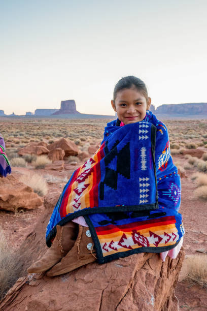 Pretty Nine Year Old Native American Navajo Indian Girl In the Early Morning Hours Dressed in Traditional Clothing Posing in Front of the Monument Valley Tribal Park stock photo