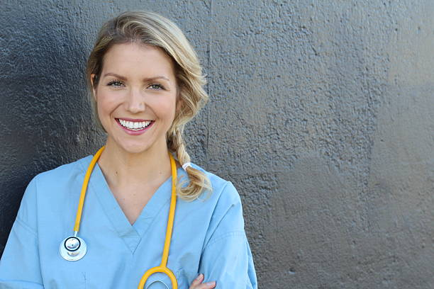 pretty nurse in uniform smiling at camera - suivi des malades photos et images de collection