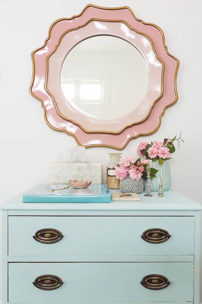 Pretty pastel blue and pink styled dressing table bedroom decor with flowers and mirror stock photo