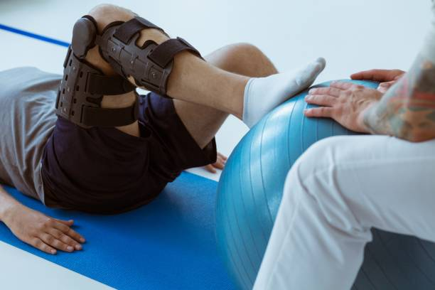 Pretty patient sitting on the blue mat in the gym and training with the ball stock photo