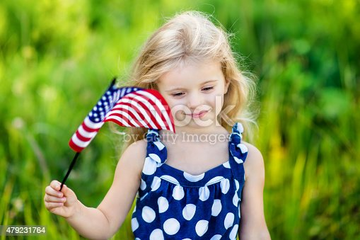 514069232 istock photo Pretty pensive little girl with blond hair holding american flag 479231764