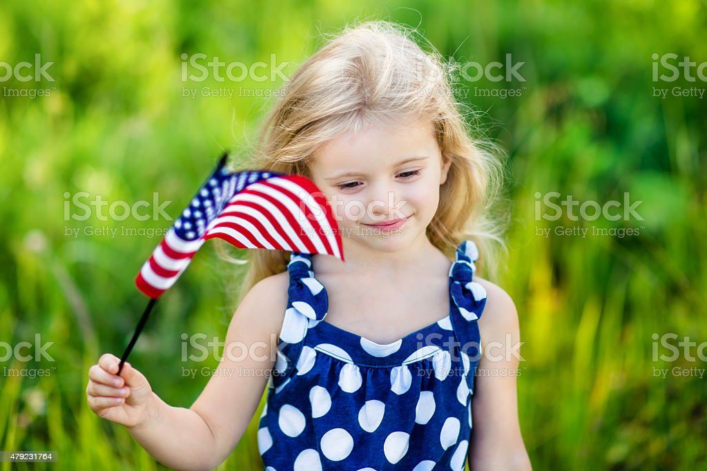 Pretty pensive little girl with blond hair holding american flag stock photo