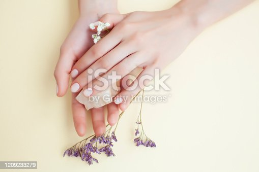 946930880 istock photo pretty perfect woman hands with white manicure and little flowers on yellow background 1209233279