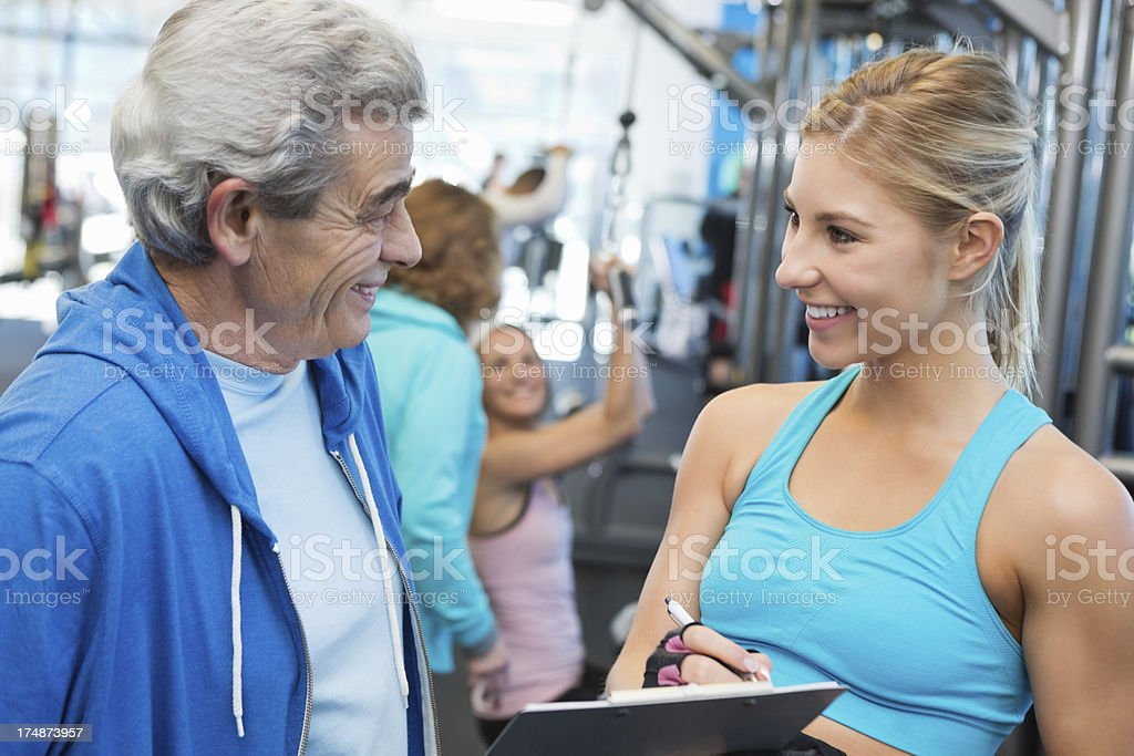 Pretty personal trainer giving senior man tour of gym facility royalty-free stock photo