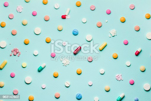 A photo of different medicinal drugs, tablets and pills on blue background.