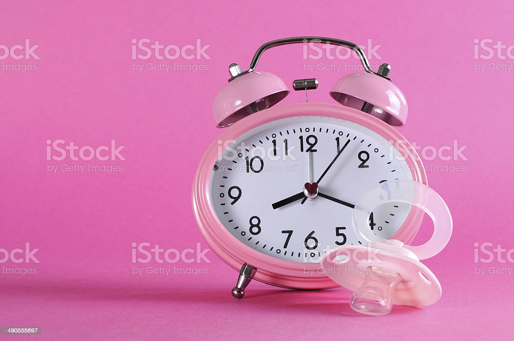 Pretty pink vintage retro style alarm clock with dummy pacificer royalty-free stock photo