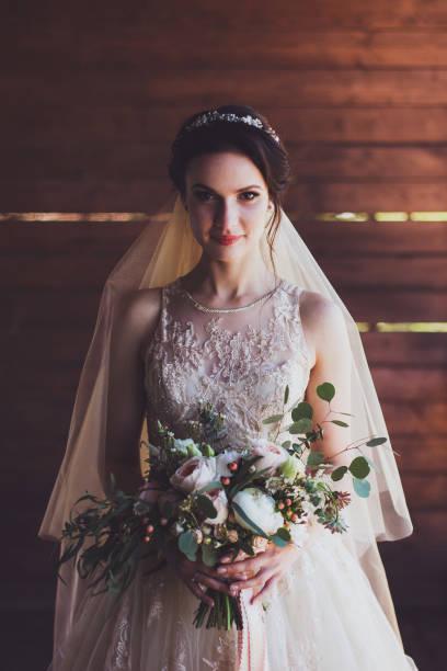 hübsche porträt der jungen schönen braut hält blumen blumenstrauß rustikalen stil - verlobungskleider stock-fotos und bilder