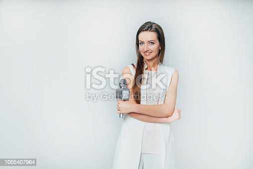istock pretty presenter holds in her hand a microphone on a white background in the studio. 1055407964
