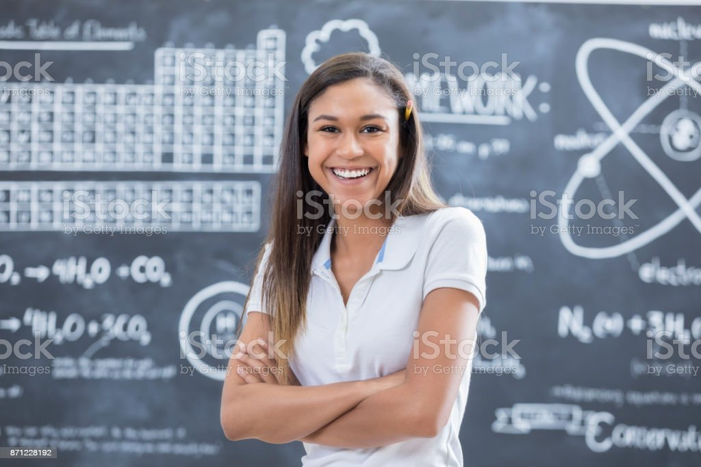 pretty private high school standing in front of chalkboard stock