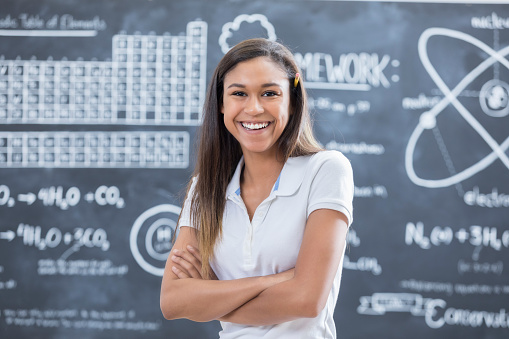 Smart mixed race high school student stands confidently in front of the chalkboard in science classroom.