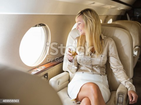 istock Pretty professional woman drinking champagne on board private jet 469958563